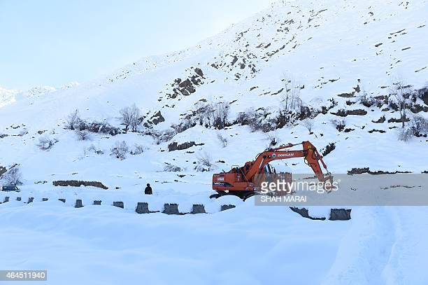 An Afghan policeman keeps watch as an excavator clears snow from a road near an avalanche site at Dara Keraman district of Panjshir province north of...
