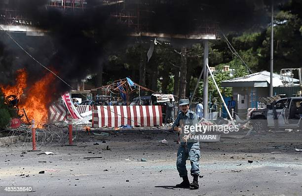 An Afghan policeman keeps watch at the site of a huge blast near the entrance of Kabul's international airport in Kabul on August 10 2015 A huge...
