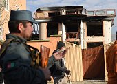 An Afghan policeman keeps watch outside the gate of a foreign compound following an attack by Taliban militants in Kabul on November 30 2014 Taliban...