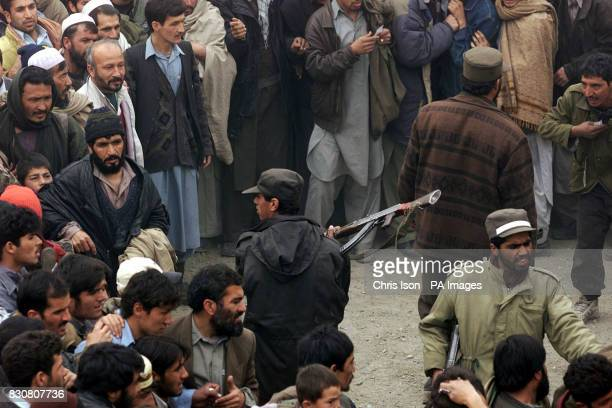 An Afghan policeman lashes out with his rifle butt to stop men attempting to climb the walls to get into watch a soccer match at the Olympic Stadium...