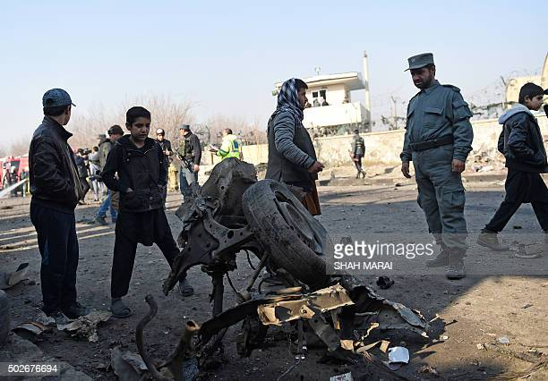 An Afghan policeman looks at the wreckage of a car which was used in a suicide car bomb near the international airport in Kabul on December 28 2015 A...