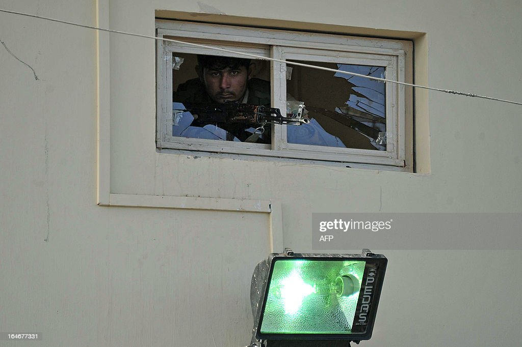 An Afghan policeman looks from a shattered window at the site of suicide attacks near a police station in Jalalabad on March 26, 2012. A group of seven suicide bombers attacked a police base in the eastern Afghan city of Jalalabad, killing five officers, police said. One bomber set off a large explosion at the entrance of the quick reaction police headquarters before two bombers blew themselves up inside the facility and four others died in a gun fight with police. AFP PHOTO / Noorullah Shirzada