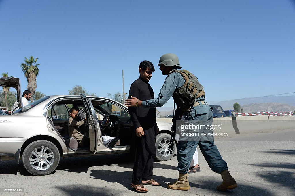 An Afghan policeman (R) searches a passenger in the city of Jalalabad, close to the border with Pakistan, on April 29, 2016, after reports that an aid worker from Perth has been kidnapped by armed men in Jalalabad. Australia was scrambling on April 29 to verify reports that an aid worker from Perth has been kidnapped by armed men in Afghanistan. The woman was taken in the city of Jalalabad, close to the border with Pakistan, on April 28, a government official in the area told AFP. / AFP / NOORULLAH