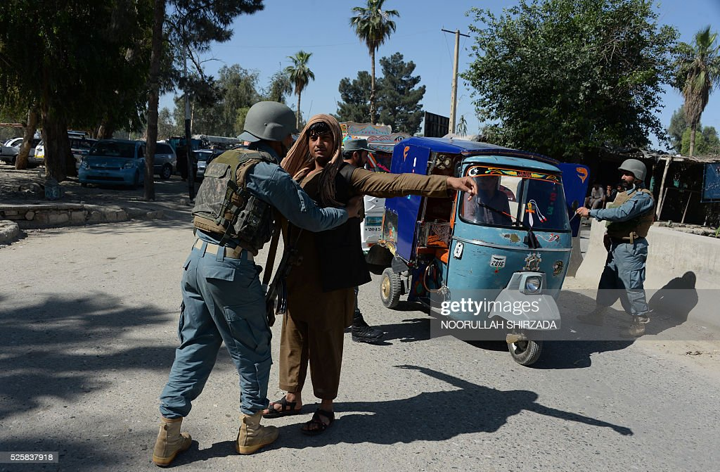 An Afghan policeman searches a passenger in the city of Jalalabad, close to the border with Pakistan, on April 29, 2016, after reports that an aid worker from Perth has been kidnapped by armed men in Jalalabad. Australia was scrambling on April 29 to verify reports that an aid worker from Perth has been kidnapped by armed men in Afghanistan. The woman was taken in the city of Jalalabad, close to the border with Pakistan, on April 28, a government official in the area told AFP. / AFP / NOORULLAH