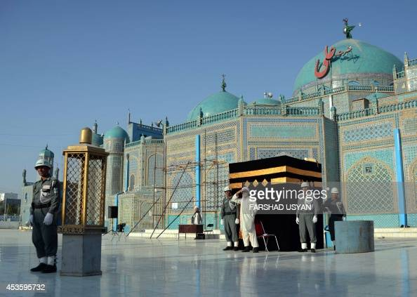 An Afghan policeman stands guard as Hajj pilgrims undergo a training workshop with a replica of the Holy Kaaba Sharif erected in the courtyard of the...