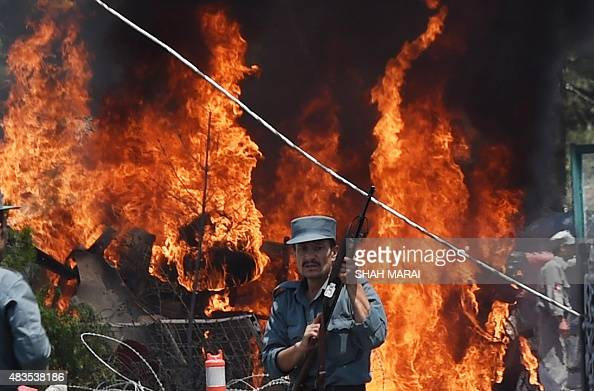 An Afghan policeman stands guard as smoke and flames rise from the site of a huge blast struck near the entrance of Kabul's international airport in...