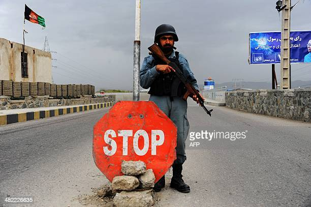 An Afghan policeman stands guard at a checkpost in the southern entrance of the northwestern city of Herat on April 3 2014 Afghans will vote on April...