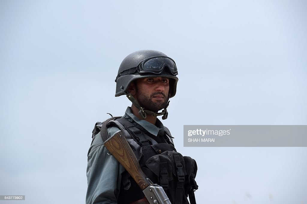 An Afghan policeman stands guard at the site of a bomb attack on the outskirts of Kabul on June 30, 2016. At least 27 policemen were killed and 40 wounded after a bomb attack claimed by the Taliban struck a convoy of buses transporting police cadets in Kabul, the interior ministry said. / AFP / SHAH