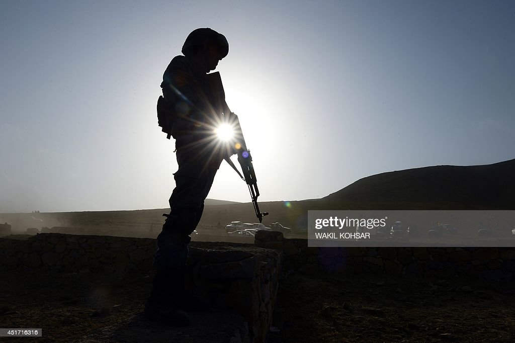 An Afghan policeman stands guard at the site of an overnight attack by Taliban militants on fuel trucks in ChawkeArghandi on outskirts of Kabul on...