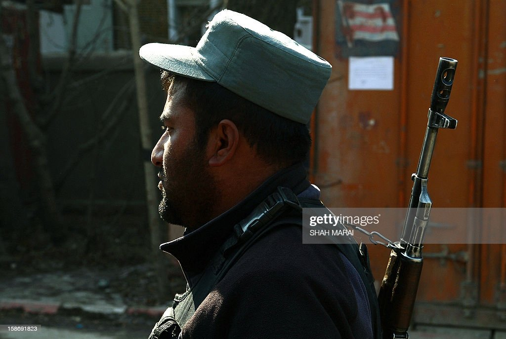 An Afghan policeman stands guard at the site where a female police officer shot dead a foreign civilian adviser at police headquarters in Kabul on December 24, 2012. A female Afghan police officer has shot dead a foreign civilian adviser in Kabul police headquqarers in an apparent 'green on blue' attack, the first of its kind by a woman, officials said. AFP PHOTO/ SHAH Marai