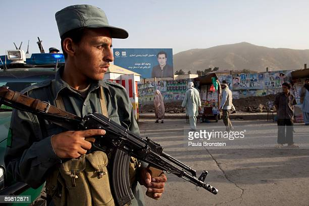 An Afghan policeman stands guard in downtown Kabul after a suicide car bomb exploded near the main gate of the NATO headquarters killing seven and...