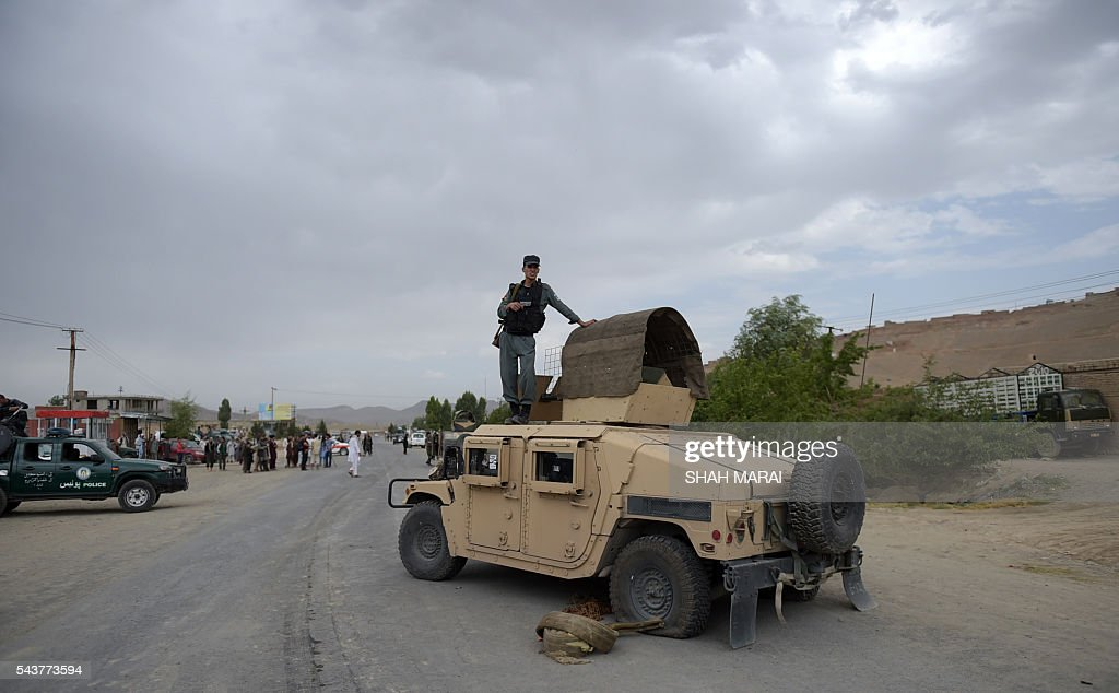 An Afghan policeman stands on the top of a Humvee vehicle as he keeps watch at the site of a bomb attack on the outskirts of Kabul on June 30, 2016. At least 27 policemen were killed Thursday and 40 wounded after a bomb attack claimed by the Taliban struck a convoy of buses transporting police cadets in Kabul, the interior ministry said. / AFP / SHAH