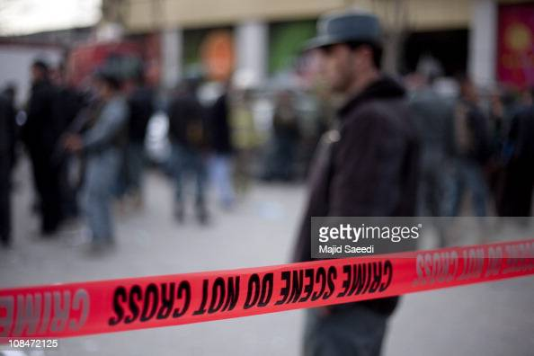 An Afghan policeman walks over shards of glass and paper at the site of an explosion near 'Finest' supermarket on January 28 2011 in Wazir Akbar Khan...