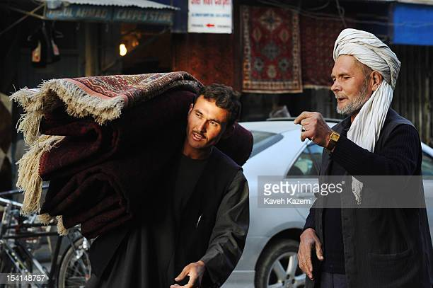 An Afghan porter carries rugs on his shoulder in Chicken Street on October 17 2011 in Kabul Afghanistan Chicken Street has been a focus for...