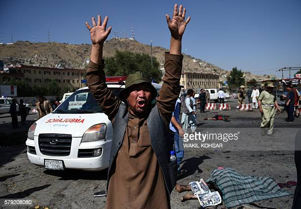 An Afghan protester screams near the scene of a suicide attack that targeted crowds of minority Shiite Hazaras during a demonstration at the Deh...