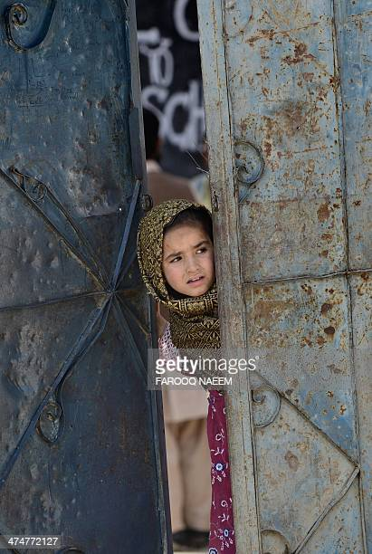 An Afghan refugee child stands in the doorway of her school at a refugee camp in Haripur on February 25 2014 The Pakistani government in...