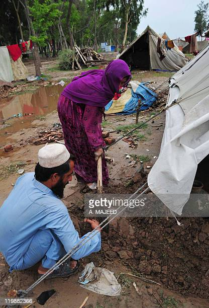 An Afghan refugee family residing in Pakistan who survived last year's flooding dig a moat around their tent at a camp in Nowshera on July 26 2011...