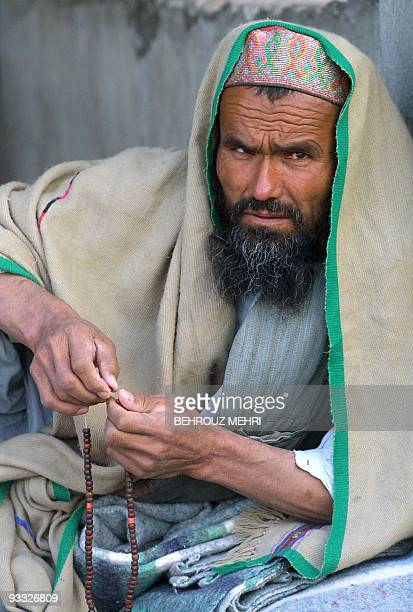 An Afghan refugee holds his prayer beads 10 October 2001 at the Shahid Arbabi temporary care camp in Iran's southeastern city of Zahedan after...