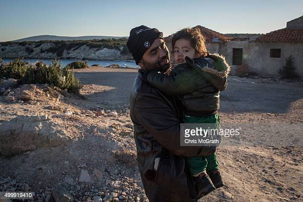 An Afghan refugee holds his son as they wait for boats to leave Turkey at a boat launching point in the coastal town of Cesme on December 4 2015 in...