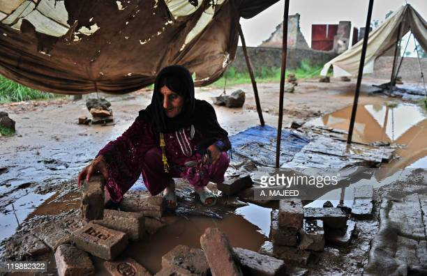 An Afghan refugee residing in Pakistan who survived last year's flooding arranges bricks at her tent in Nowshera on July 26 2011 Pakistan has failed...