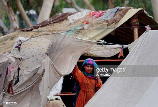 An Afghan refugee residing in Pakistan who survived last year's flooding looks on fron her tent at a camp in Nowshera on July 26 2011 Pakistan has...
