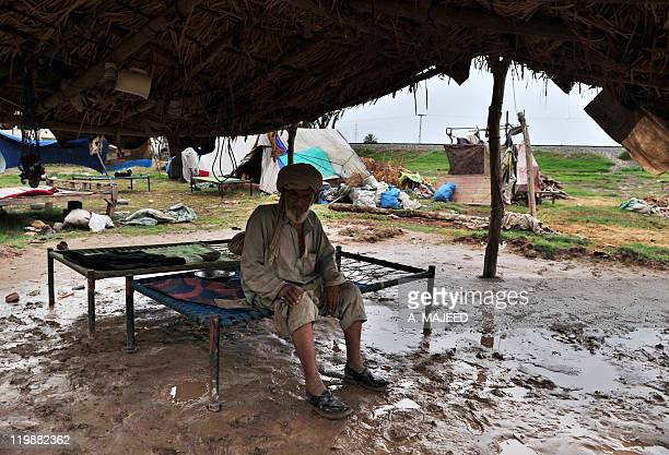An Afghan refugee residing in Pakistan who survived last year's flooding looks on underneath a tent at a camp in Nowshera on July 26 2011 Pakistan...