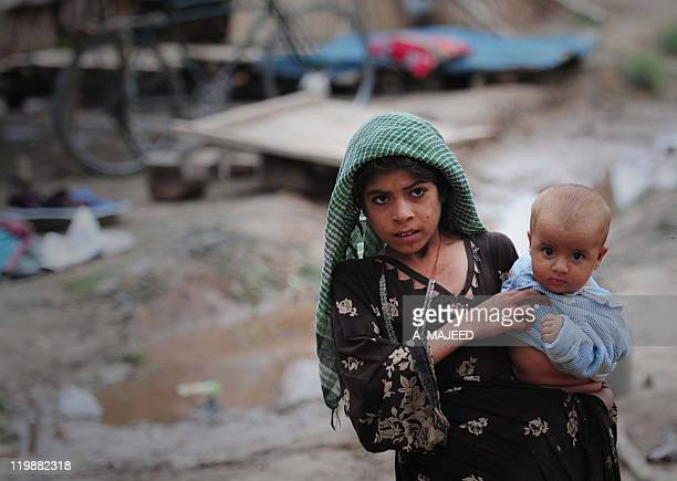 An Afghan refugee residing in Pakistan who survived last year's flooding walks at a camp in Nowshera on July 26 2011 Pakistan has failed to invest in...