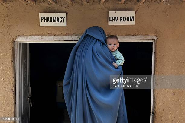 An Afghan refugee woman carries her child at a special medical camp organised by UNHCR with the coordination of Pakistan Medical Dental Association...