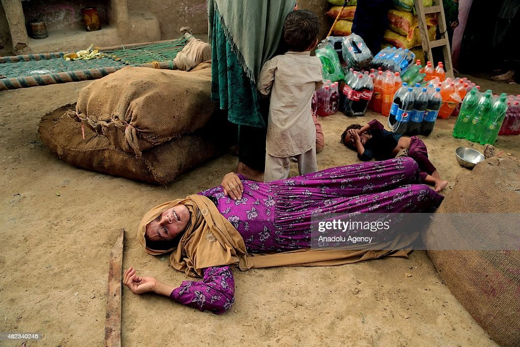 An Afghan refugee woman passes out during the Pakistani officials' attempt to demolish the refugee village to conduct Islamabad's High Court's decision at a refugee village on the outskirts of Islamabad, Pakistan on July 30, 2015.