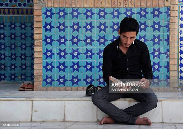 An Afghan resident reads a religious book during the Islamic holy month of Ramadan at the Hazrat Ali shrine or Blue Mosque in MazariSharif on July 3...