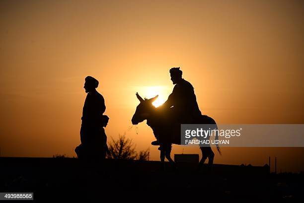 An Afghan resident rides on his donkey as the sun sets on the outskirts of Mazarisharif on May 26 2014 Afghanistan remains at war with civilians...