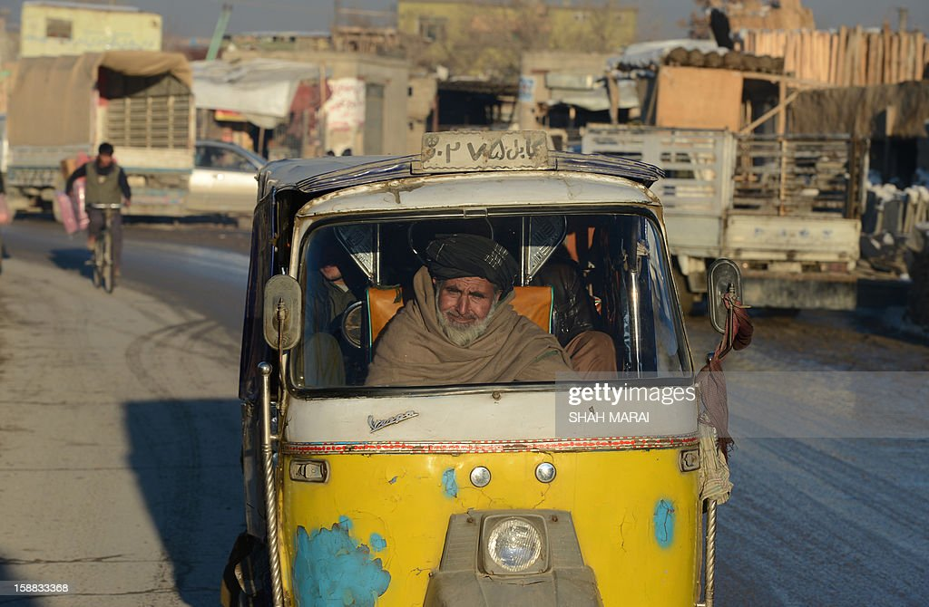 An Afghan rickshaw driver smiles as he drives in the cold weather in Kabul on December 31, 2012. Over a third of Afghans are living in abject poverty, as those in power are more concerned about addressing their vested interests rather than the basic needs of the population, a UN report said. AFP PHOTO/ SHAH Marai