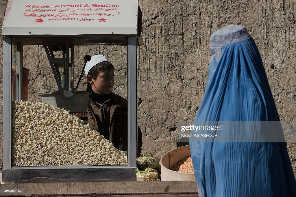 An Afghan roadside popcorn vendor (L) waits for costumers as a burqa-clad pedestrian walks past in Kabul on February 15, 2014. Some nine million Afghans or 36 percent of the population are living in 'absolute poverty' while another 37 percent live barely above the poverty line, according to a UN report. AFP PHOTO/ Nicolas ASFOURI