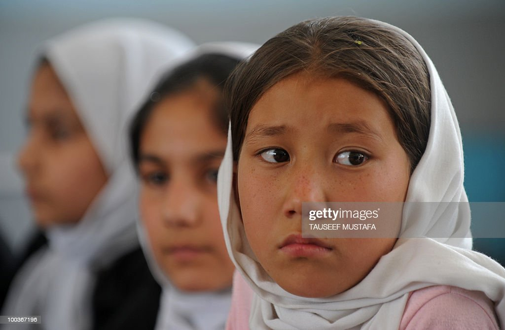 An Afghan schoolgirl looks on during a World Teacher's Day function at a school in central Kabul on May 24, 2010. Afghanistan has been suffering some sort of armed conflict for the past 30 years, starting with the Soviet invasion of 1979, through civil war and, from 1996-2001, rule by the Islamist Taliban who banned girls from education. This has left a huge knowledge gap that the international community has been trying to fill, with billions of dollars of aid pouring in since the Taliban were pushed out in a US-led invasion. AFP PHOTO/Tauseef MUSTAFA