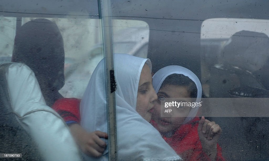An Afghan schoolgirl looks on from inside a vehicle on a rainy day in Kabul on November 6, 2013. Despite massive injections of foreign aid since the fall of the Taliban in 2001, Afghanistan remains desperately poor as it attempts to recover from decades of conflict. AFP PHOTO / Farshad USYAN