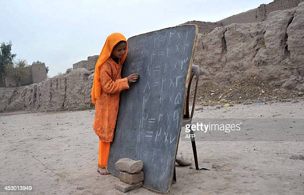 An Afghan schoolgirl writes an a blackboard at an open classroom of a refugee camp on the outskirts of Jalalabad Nangarhar province on December 1...