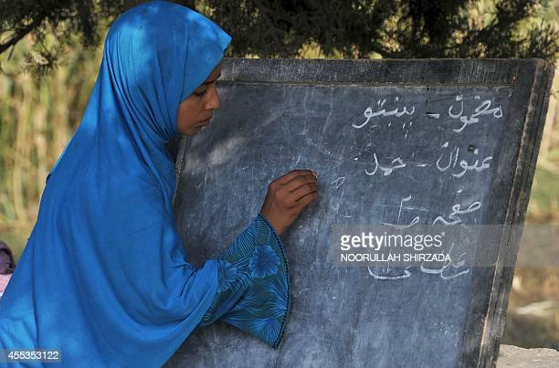 An Afghan schoolgirl writes on a blackboard at an open classroom on the outskirts of Jalalabad Nangarhar province on September 13 2014 Afghanistan...