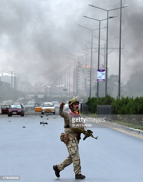 An Afghan security official gestures as he runs at the site of an attack in front of Parliament building in Kabul on June 22 2015 Taliban militants...