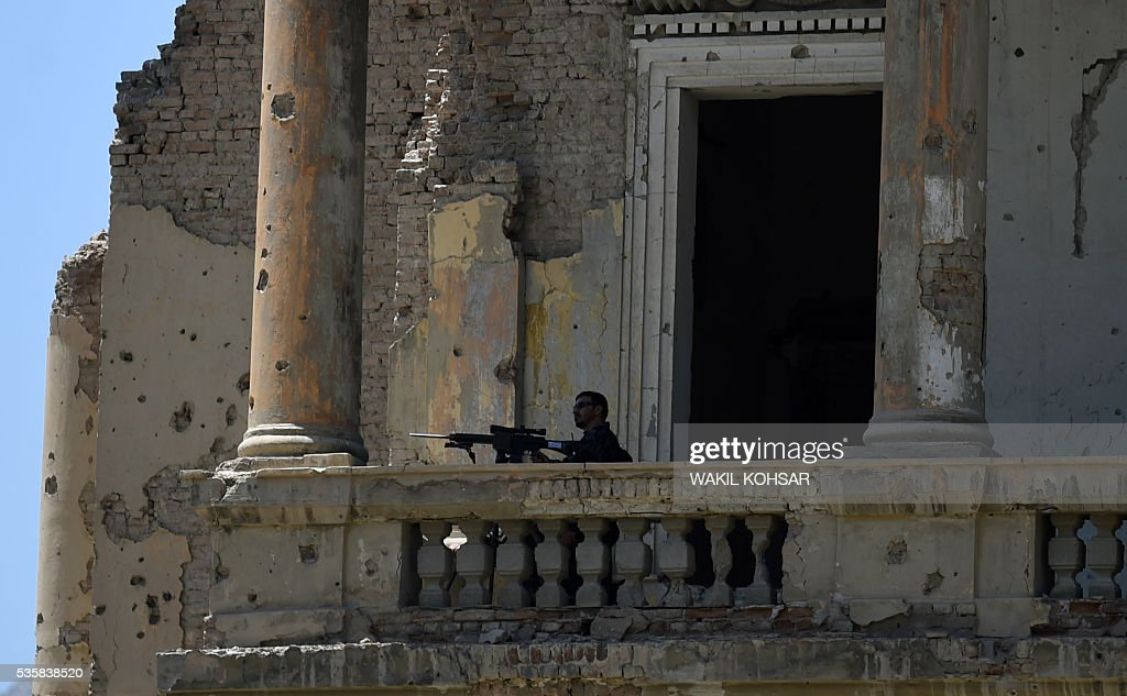 An Afghan security official stands on a balcony of the ruined Darul Aman Palace in Kabul on May 30, 2016. Afghan President Ashraf Ghani has launched restoration work at Kabul's historic Darul Aman Palace, whose bombed out ruins have long symbolised the suffering caused by the country's decades-long conflict. The once-grand hilltop palace at the edge of Kabul was also the venue of Ghani's cabinet meeting on May 30, the first such official gathering there in nearly a century. KOHSAR