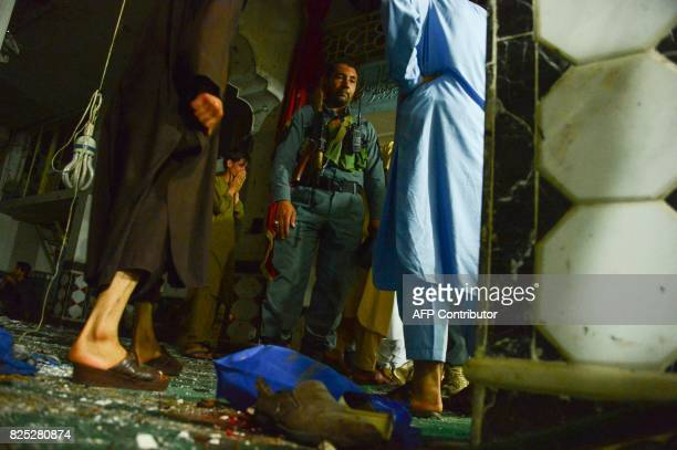 An Afghan security personel inspects the site of a suicide bomb attack at a Shiite mosque in Herat on August 1 2017 A suicide bomber and a gunman...
