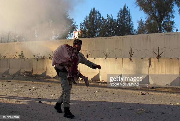 An Afghan security personnel carries an injured civilian after a suicide bomb attack that targeted foreign military forces in Lashkargah city capital...