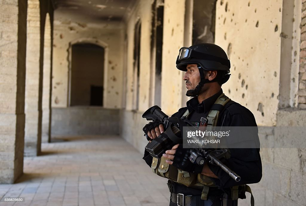 An Afghan security personnel keeps watch as Afghan President Ashraf Ghani inaugurates the renovation of the former royal Darul Aman Palace in Kabul on May 30, 2016. Afghan President Ashraf Ghani on May 30, 2016 launched restoration work at Kabul's historic Darul Aman Palace, whose bombed out ruins have long symbolised the suffering caused by the country's decades-long conflict. The once-grand hilltop palace at the edge of Kabul was also the venue of Ghani's cabinet meeting on May 30, the first such official gathering there in nearly a century. KOHSAR