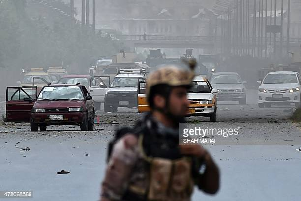 An Afghan security personnel runs at the site of an attack in front of Parliament building in Kabul on June 22 2015 Taliban militants attacked the...