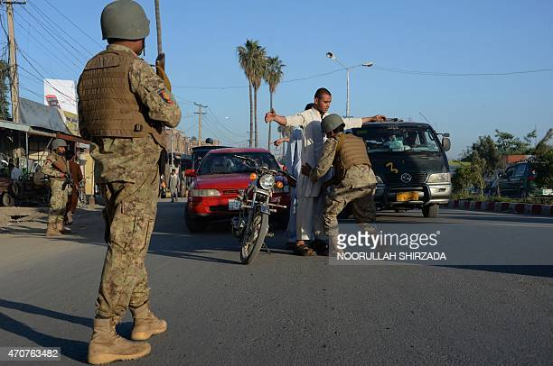 An Afghan security personnel searches commuters as others look on at a checkpoint in Jalalabad in Nangarhar province on April 22 2015 The Afghan...