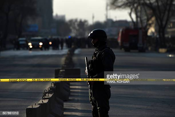 An Afghan security personnel stands guard near the site of a suicide attack at the entrance to a police base in Kabul on February 1 2016 A Taliban...