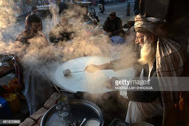 An Afghan shopkeeper boils milk as he waits for customers at dawn in Jalalabad in Nangarhar province on January 16 2015 Afghanistan's economy has...