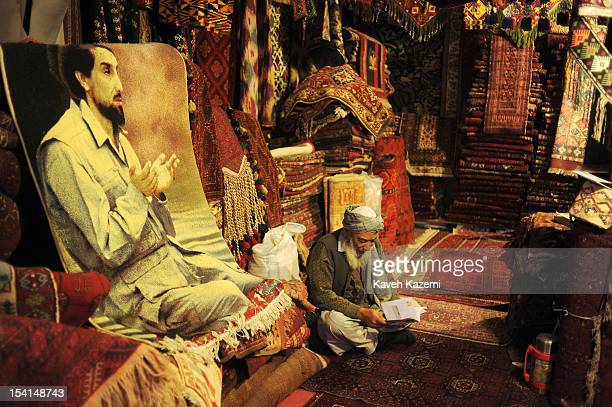 An Afghan shopowner surrounded by carpets and rugs seen sits behind a rug imprinted with image of assasinated Afghan Mujahedin commander Ahmad Shah...