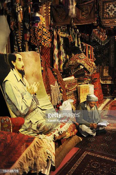 An Afghan shopowner surrounded by carpets and rugs seen sits reading behind a rug imprinted with image of assasinated Afghan Mujahedin commander...