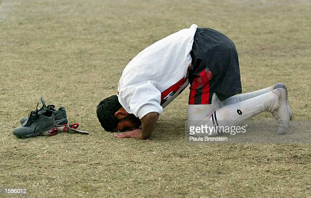 An Afghan soccer player prays during a break in a match at the Kabul Olympic stadium November 4 2002 in Kabul Afghanistan Both teams Maihan and Sulha...