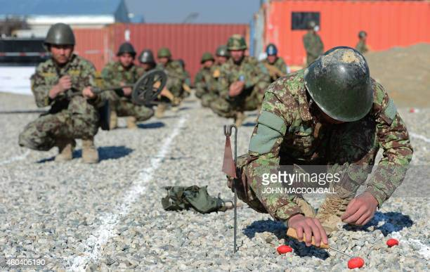 An Afghan soldier digs up a mine during a demining drill at camp Shaheen a training facility for the Afghan National Army located west of Mazare...